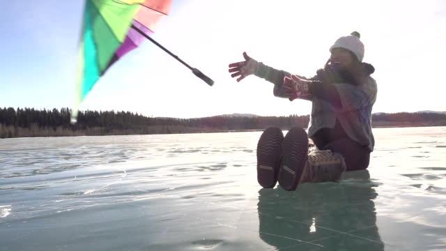 vídeos de stock, filmes e b-roll de mulher libera o guarda-chuva no lago congelado, sopé - mitten