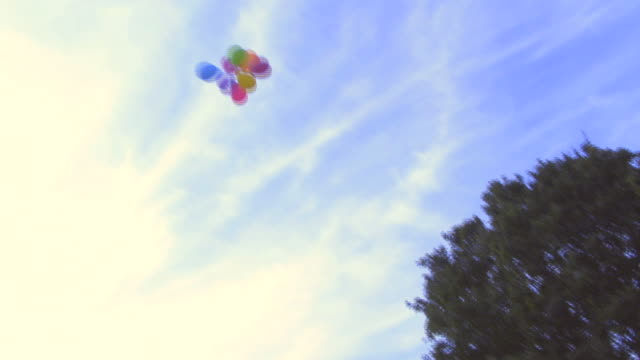 Woman releasing balloons into the air; UK