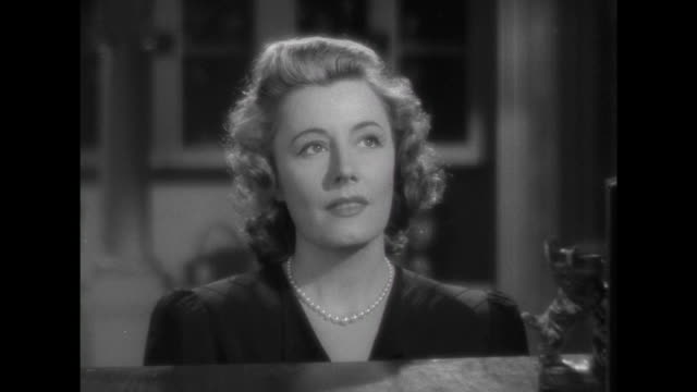 stockvideo's en b-roll-footage met 1941 woman (irene dunne) reminisces as she listens to a love song - huppelen