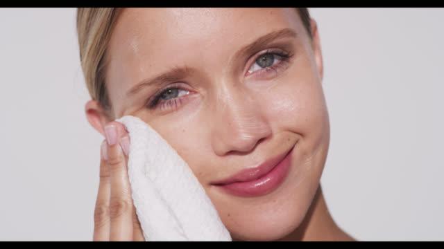 vidéos et rushes de woman removes cleanser from face with cloth - appliquer