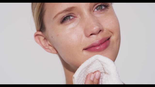 woman removes cleanser from face with cloth - pelle umana video stock e b–roll