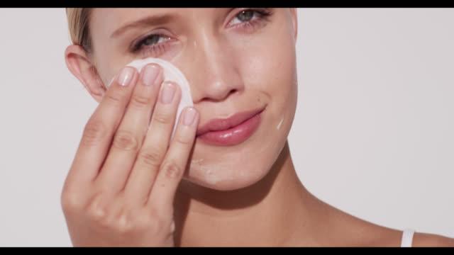 vidéos et rushes de woman removes cleanser from face with cotton pad - propreté