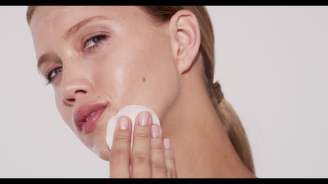 woman removes cleanser from face with cotton pad - strofinare toccare video stock e b–roll