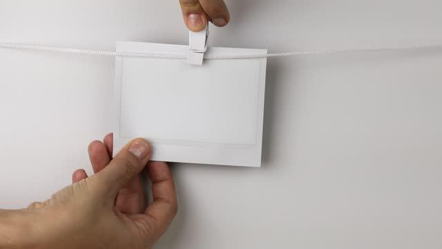 vídeos y material grabado en eventos de stock de mujer quitando marco de fotos instantáneas en blanco - transferencia de impresión instantánea
