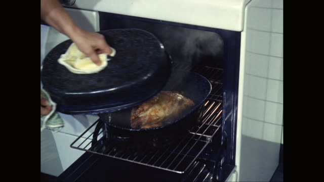 vídeos de stock, filmes e b-roll de cu tu woman removing chicken meat from oven in domestic kitchen / united states - domestic kitchen
