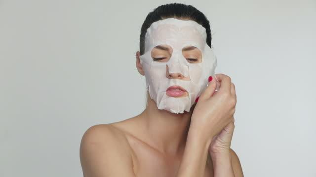 vídeos de stock, filmes e b-roll de mulher eliminar tecido máscara facial hidratante - cirurgia plástica