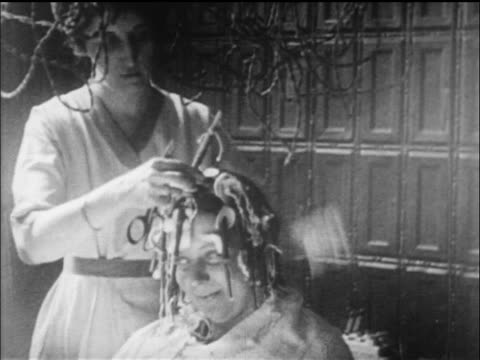 B/W 1919 woman removing electric curlers from other woman's hair in beauty parlor / newsreel