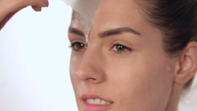 Woman removing facial peel off mask
