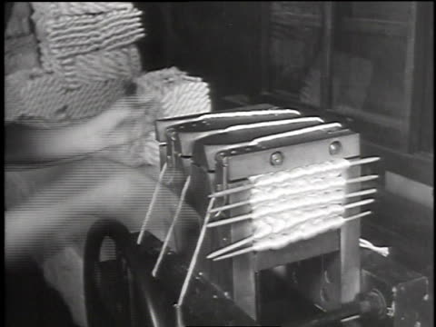 woman removing finished silk skein from winding machine / woman packing skeins into bundles with a machine / bundles of skeins packed into bales for... - 絹点の映像素材/bロール