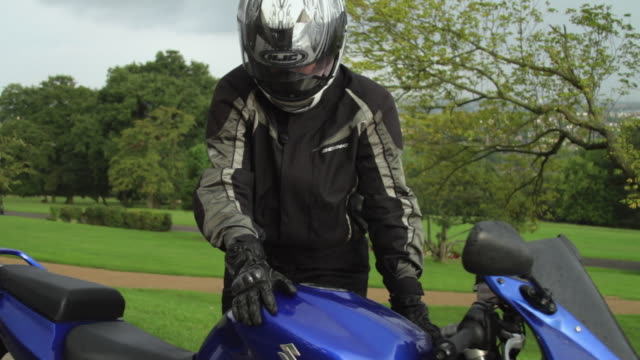 MS Woman removing helmet, standing by motorcycle in park / London, United Kingdom