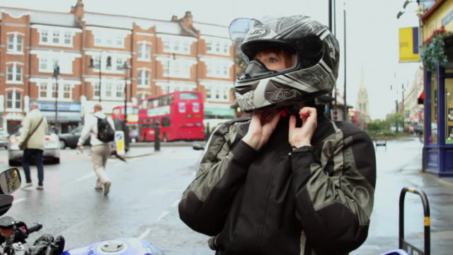 MS Woman removing helmet, standing by motorcycle on street / London, United Kingdom