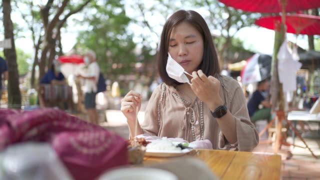 frau entfernt ihre schützende gesichtsmaske, bevor sie etwas essen auf dem straßenmarkt im freien unter baum - entfernt stock-videos und b-roll-filmmaterial