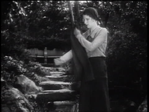 b/w 1931 rear view woman removing jacket + walking up stairs in park away from camera - 1931 stock videos & royalty-free footage