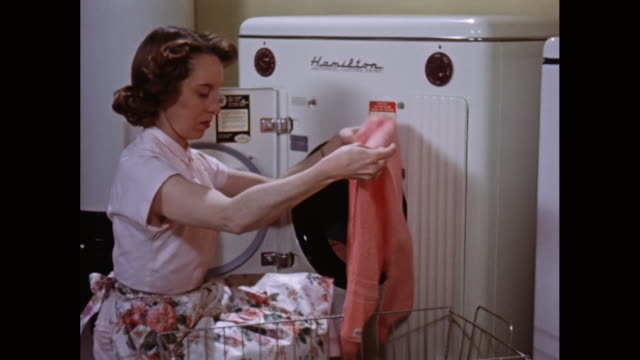 ms woman removing laundry from washing machine into basket / united states - 1950点の映像素材/bロール