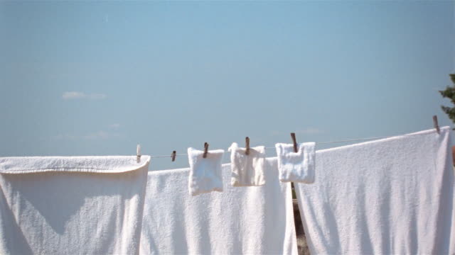 woman removing laundry hanging from clothesline / saint-ferme, france - wäschekorb stock-videos und b-roll-filmmaterial