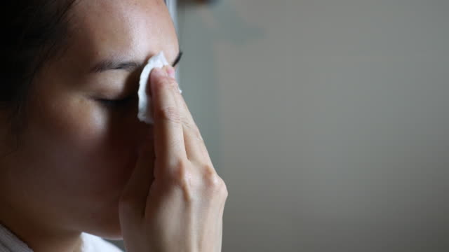 woman removing makeup from her face by cotton - applying stock videos and b-roll footage