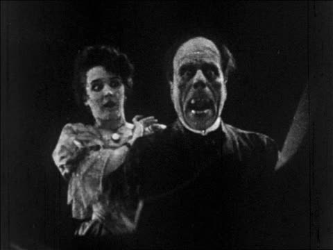 b/w 1925 woman (mary philbin) removing mask of disfigured man (lon chaney, sr.) + screams / feature - ugliness stock videos & royalty-free footage