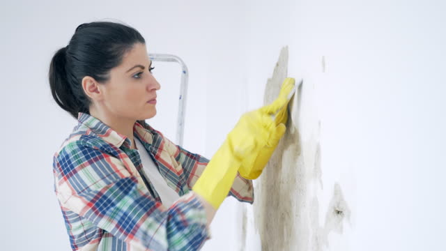 Woman removing old paint.