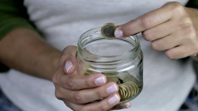 vídeos de stock e filmes b-roll de woman removing one euro coin from savings in jar - segurar