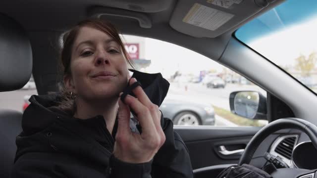 frau entfernt schützende gesichtsmaske im auto nach dem einkaufen - entfernt stock-videos und b-roll-filmmaterial