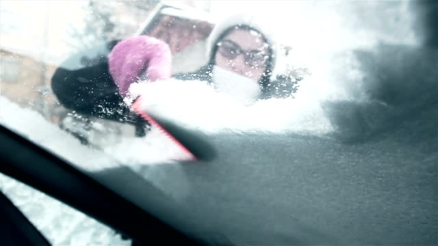 woman removing snow from car windshield - ghiacciato video stock e b–roll