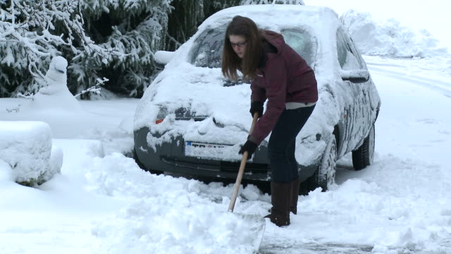 MS Woman removing snow from street / Saarburg, Rhineland-Palatinate, Germany