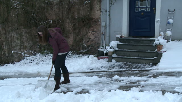 vídeos de stock e filmes b-roll de ws  woman removing snow from street / saarburg, rhineland-palatinate, germany - pá para neve