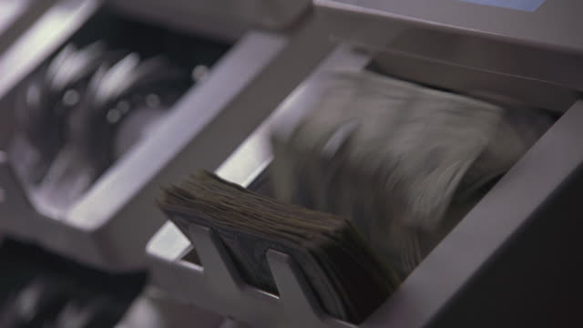A woman removing stacks of bills from a counting machine.