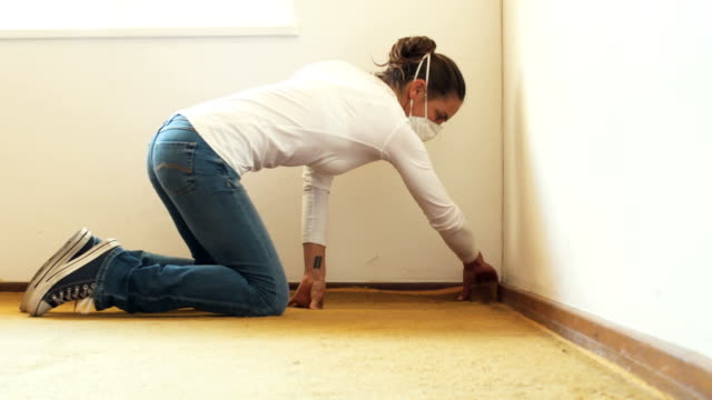 Woman renovator rips out old carpet