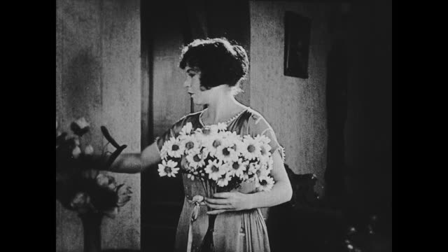 vidéos et rushes de 1922 a woman (madge kennedy) replaces a bouquet of daisies - marguerite
