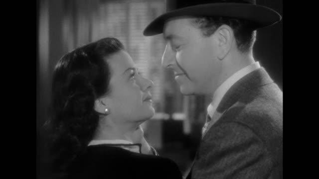 1948 CU - Woman (Joan Bennett) reprimands an amorous man (Paul Henreid) before arranging a date