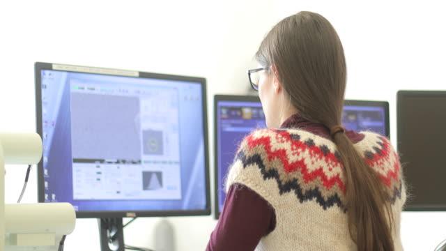 woman researcher analyzing scientific sample on computer monitor - microscopio elettronico a scansione video stock e b–roll