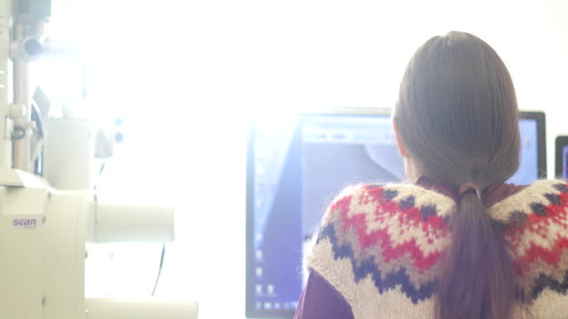 woman researcher analyzing scientific samples on computer monitor - microscopio elettronico a scansione video stock e b–roll