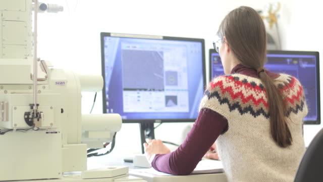 ricercatrice donna analisi campioni scientifici su monitor computer - microscopio elettronico a scansione video stock e b–roll