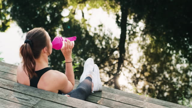 woman resting and drinking a protein shake after her exercise - protein drink stock videos & royalty-free footage