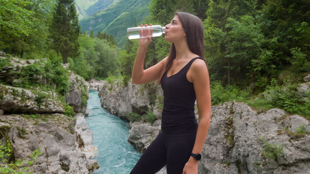 woman resting at mountain river, hydrating from a reusable water bottle - bottle stock videos & royalty-free footage