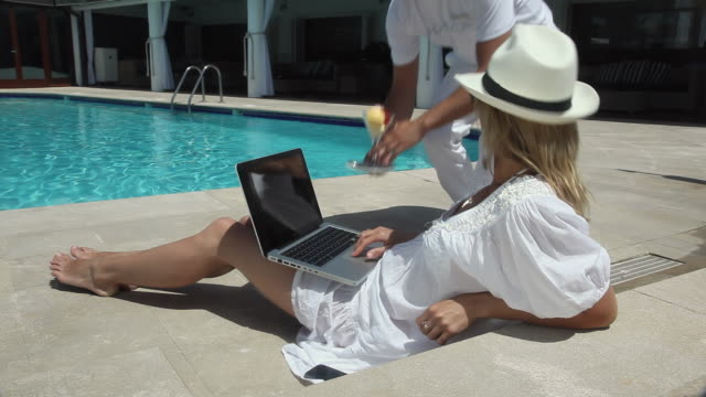 MS Woman resting by swimming pool and using laptop,  server brings ice cream / Golf De Son Termes, Bunyola, Mallorca, Baleares, Spain