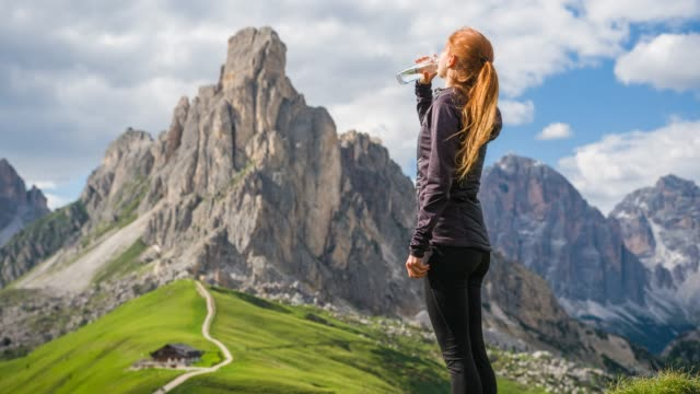 woman resting from hiking in mountains, drinking from a water bottle - mountain pass stock videos & royalty-free footage