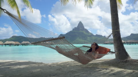 a woman resting in a hammock at a tropical island resort. - vacations stock videos & royalty-free footage