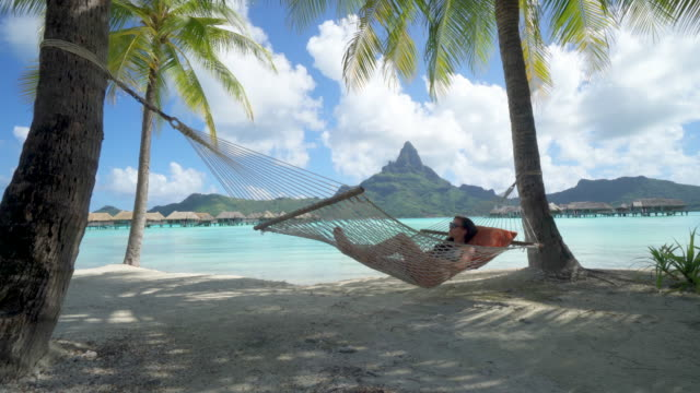 a woman resting in a hammock at a tropical island resort. - hammock stock videos & royalty-free footage