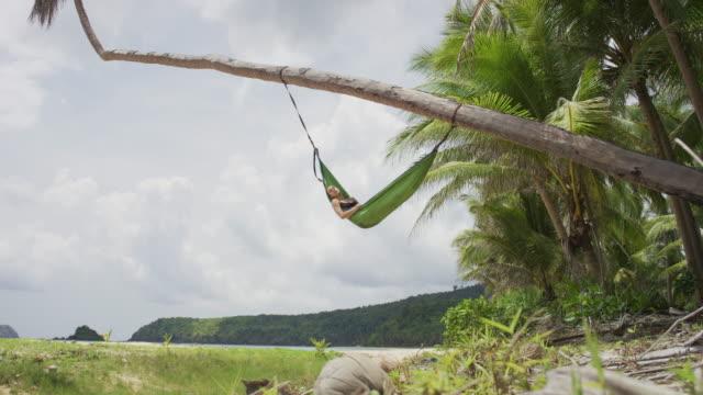 女性ヤシの木から吊り下げられたハンモックで休んで - 屋外遊具点の映像素材/bロール
