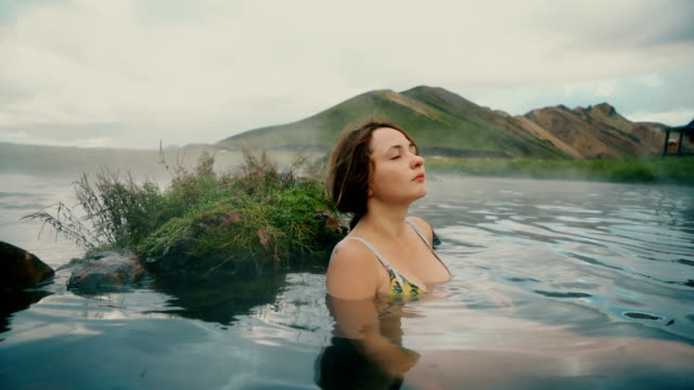 woman resting in hot natural pool in iceland - hot spring stock videos & royalty-free footage