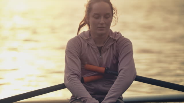woman resting in rowboat on river during sunset - three quarter length stock videos & royalty-free footage