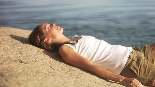 a woman resting on cliffs blido stockholm archipelago sweden. - sunbathing stock videos & royalty-free footage