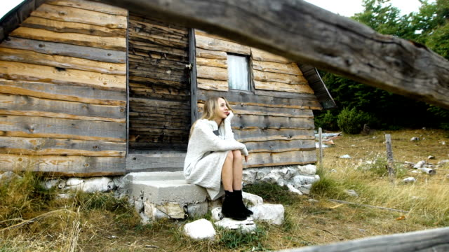 vídeos y material grabado en eventos de stock de mujer descansando en la pradera de montaña. cabaña de madera en bakcground - cabaña de madera