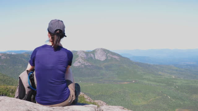 woman resting on mountain peak after hiking at parc national des grands-jardins, quebec, canada - parc national stock videos & royalty-free footage