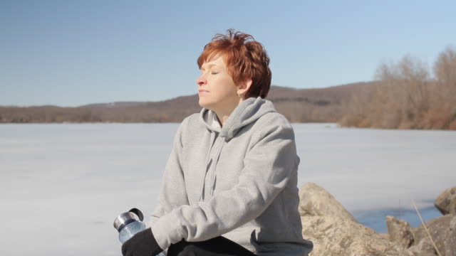 MS Woman resting on rock by frozen lake / Glen Gardner, New Jersey, USA