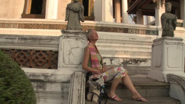 MS ZI CU Woman resting on temple steps, basking in sunlight, Wat Phra Kaew (Temple of the Emerald Buddha), Bangkok, Thailand