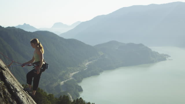 ws pan woman resting supported by rope on cliff, lake with mountains in background, squamish, british columbia, canada - extreme sports stock videos & royalty-free footage