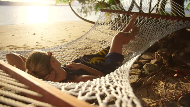 vídeos de stock, filmes e b-roll de a woman rests in a hammock at sunset on a tropical island in fiji. - rede de dormir